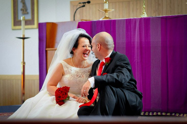 newly-wed couple happily sitting in front of church altar