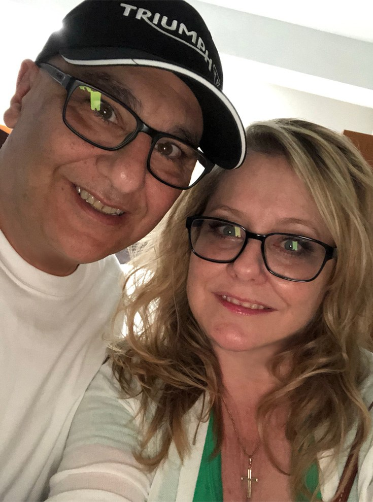 blonde, middle-aged woman with her husband wearing eyeglasses