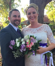 happy beautiful bride holding purple and white flowers with her handsome smiling groom