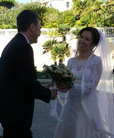 Love U success story of newly married couple laughing together while holding a wedding bouquet