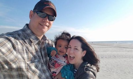 Love U success story of a woman with her baby girl and husband on the beach