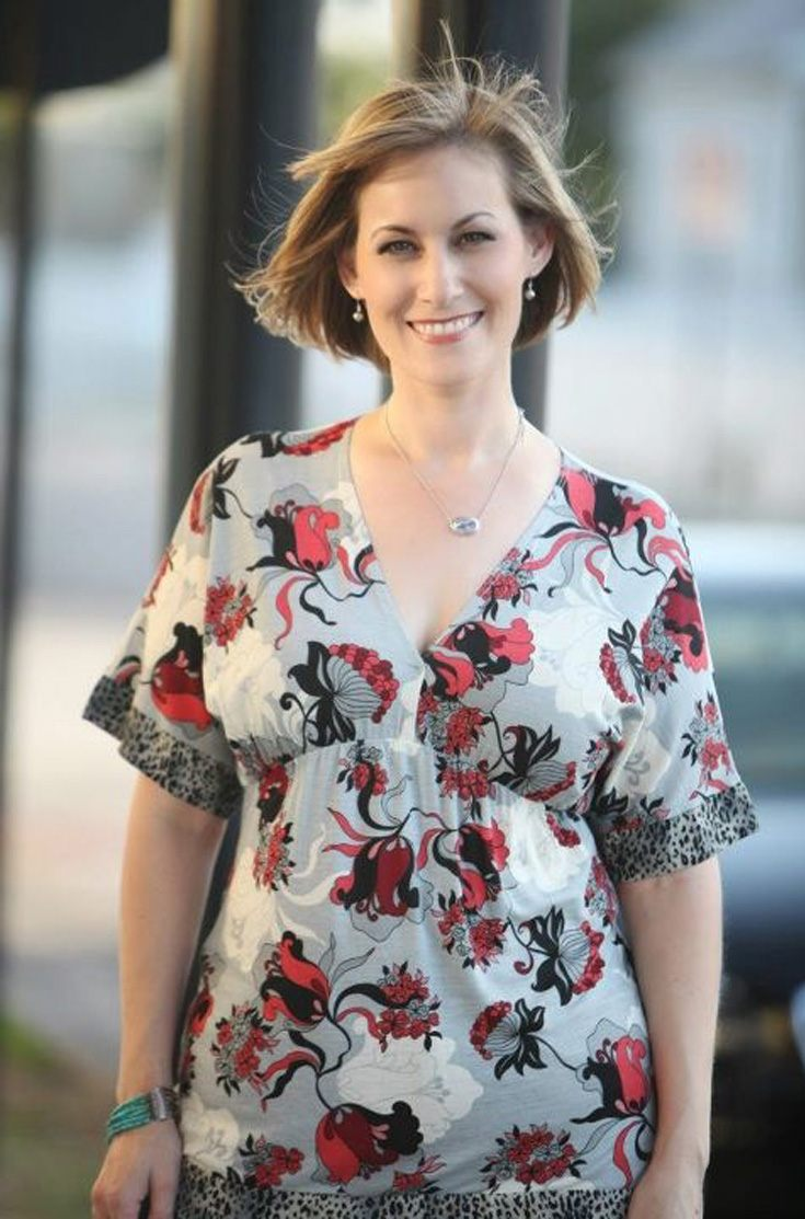 a woman with short hair wearing floral dress