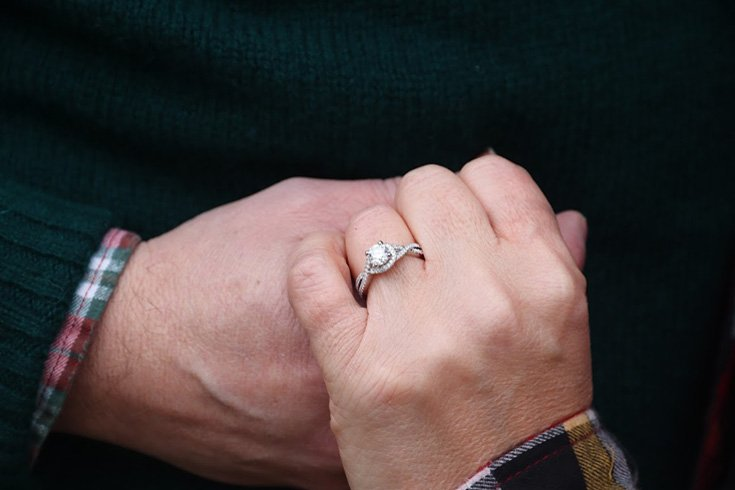 a man holding her woman's hand with an engagement ring