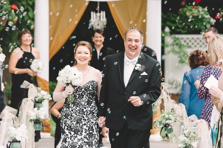 newly-wed couple walking down the isle full of bubbles