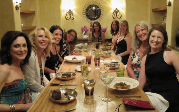 group of beautiful women sitting around dinner table smiling to the camera