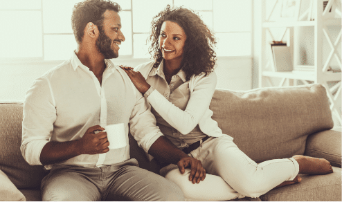 Love U success story of beautiful couple wearing all white on couch staring at each other's eyes
