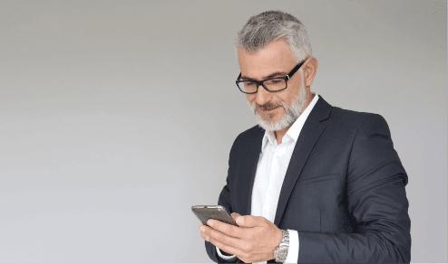 handsome older man wearing glasses checking his smartphone