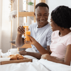 Love U success story of happy couple wearing all white having breakfast in bed