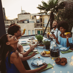 Group of friends and lovers sitting around the table eating, talking and laughing