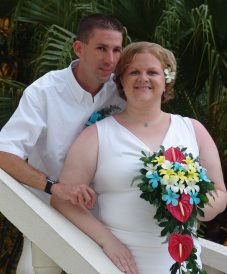 curved bride holding her bouquet with her groom at the back