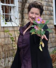 woman smiling and holding a flower finding the one online