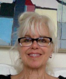 A blonde woman wearing eyeglasses taking a selfie
