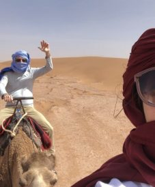 a couple in the desert riding camels