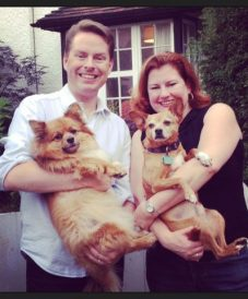 happy couple holding their 2 dogs