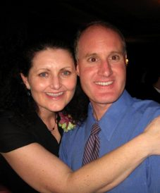 middle-aged man wearing blue longsleeves and tie, hugged by his wife