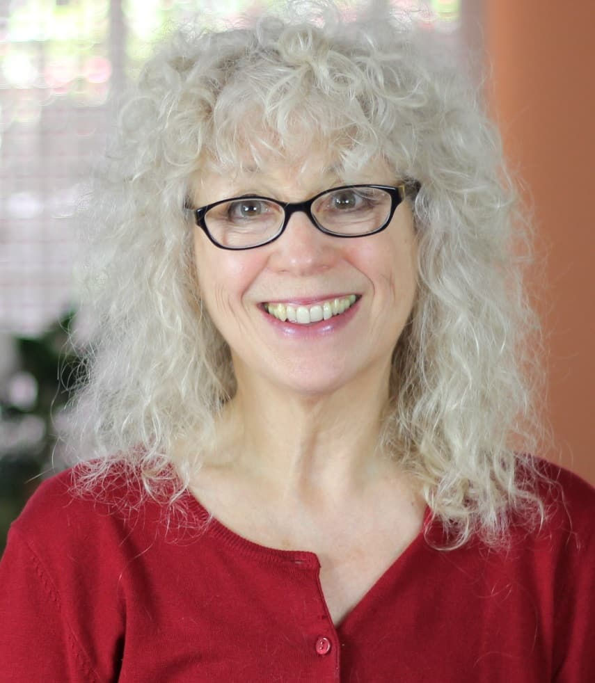 smart strong successful woman with white curly hair wearing glasses and smiling