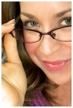 A smart, beautiful woman wearing an eye glass smiling at the camera