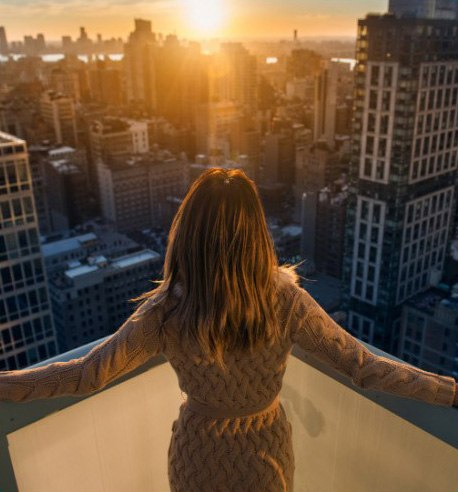 a woman on rooftop enjoying the view of beautiful sunset